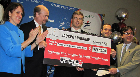 Tim Davidson, second from left; Greg Skidmore, center; and Brandon Lacoff, second from right, on Monday with a ceremonial check for $254 million won in the Connecticut Powerball on Nov. 2.