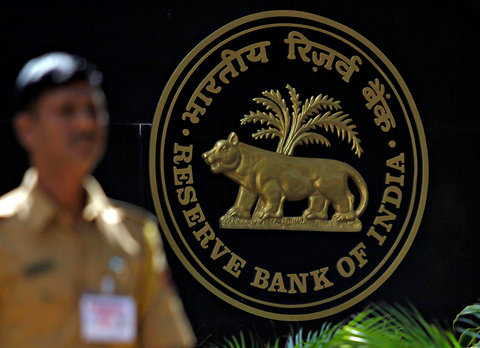 A policeman walks past the logo of the Reserve Bank of India outside its head office in Mumbai, Maharashtra in this Nov. 2, 2010 file photo.