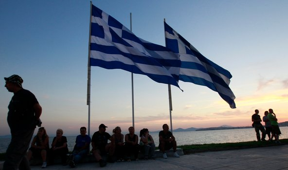 Supporters of the extreme right Golden Dawn party sit below Greek flags during an election campaign rally in Athens on Monday, June 11.
