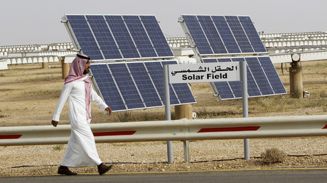 A Saudi man walks on a street past a field of solar panels © Fahad Shadeed
